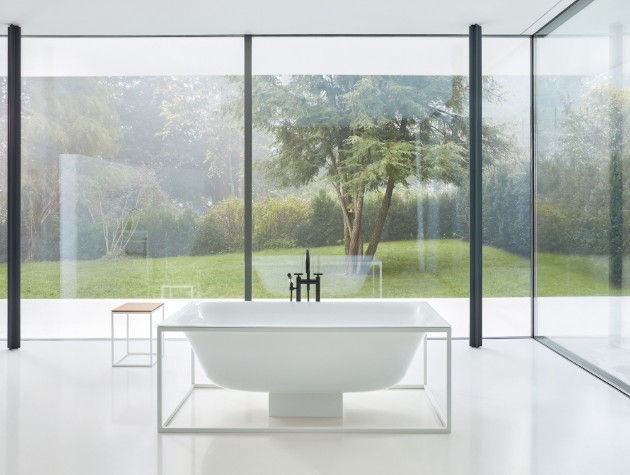A stylish steel bath in the centre of a room with windows copy